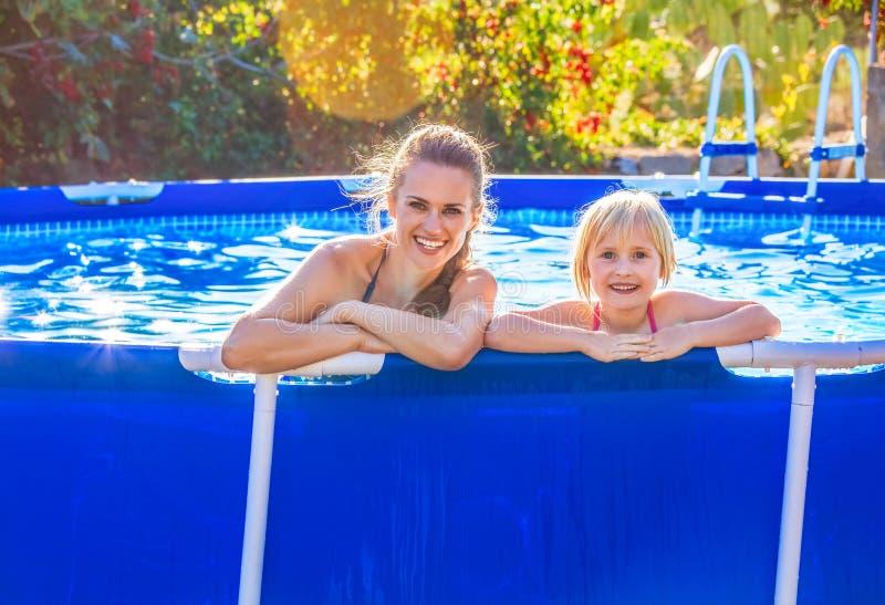 Szczęśliwa aktywny matka, dziecko w pływackiego basenu relaksować i obrazy royalty free