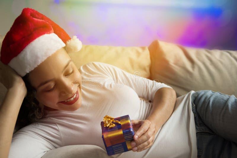 Szczęśliwa amerykanin afrykańskiego pochodzenia kobieta jest ubranym Santa kapeluszowy patrzeje Christ zdjęcia stock