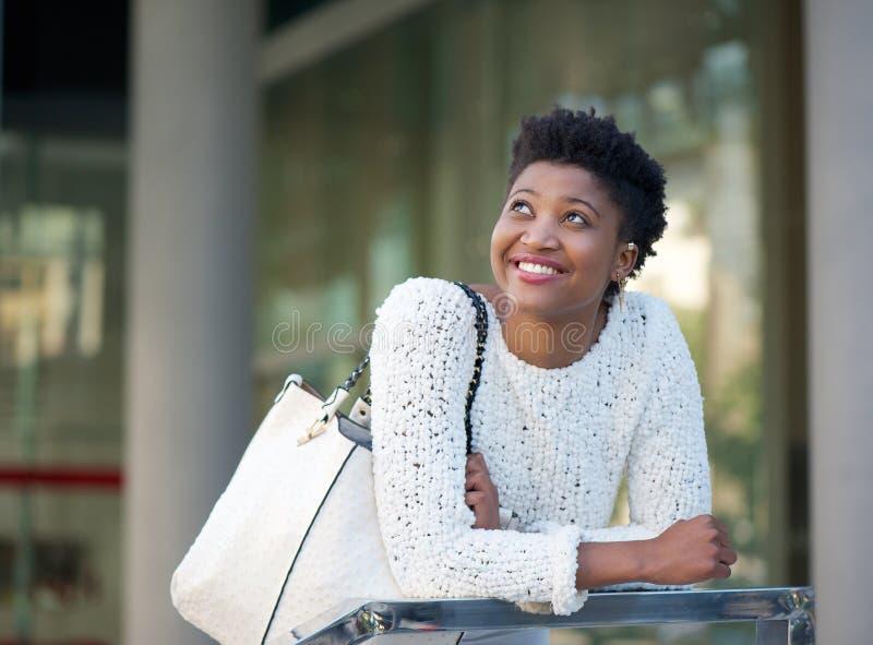 Szczęśliwa amerykanin afrykańskiego pochodzenia kobieta ono uśmiecha się w mieście fotografia stock