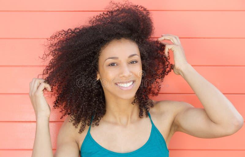 Szczęśliwa amerykanin afrykańskiego pochodzenia kobieta ono uśmiecha się z ręką w włosy obraz royalty free