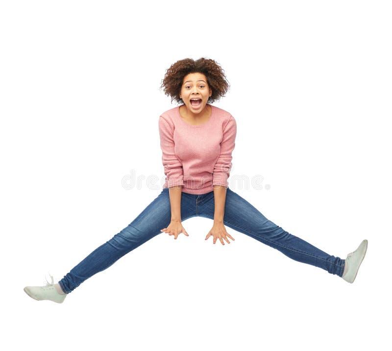 Szczęśliwa amerykanin afrykańskiego pochodzenia kobieta skacze nad bielem fotografia stock