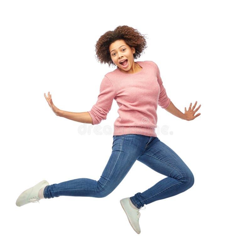 Szczęśliwa amerykanin afrykańskiego pochodzenia kobieta skacze nad bielem zdjęcie royalty free