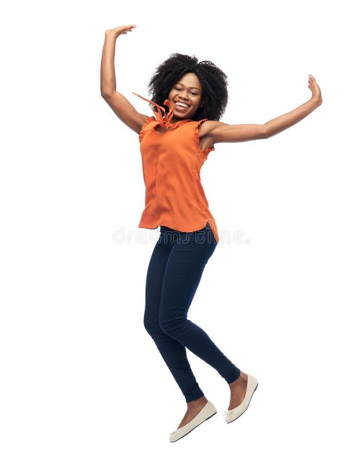 Szczęśliwa amerykanin afrykańskiego pochodzenia kobieta skacze nad bielem zdjęcia royalty free