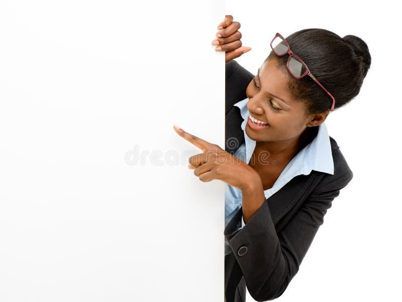 Szczęśliwa amerykanin afrykańskiego pochodzenia kobieta wskazuje przy billboardu znaka bielu tłem zdjęcia stock