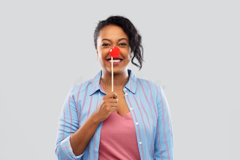Szczęśliwa amerykanin afrykańskiego pochodzenia kobieta z czerwonym błazenu nosem zdjęcie stock