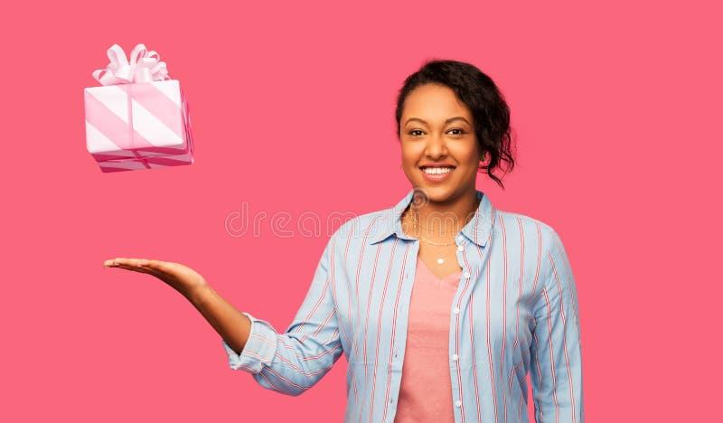 Szczęśliwa amerykanin afrykańskiego pochodzenia kobieta z prezentem urodzinowym fotografia royalty free