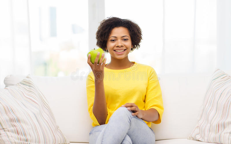 Szczęśliwa amerykanin afrykańskiego pochodzenia kobieta z zielonym jabłkiem obrazy royalty free