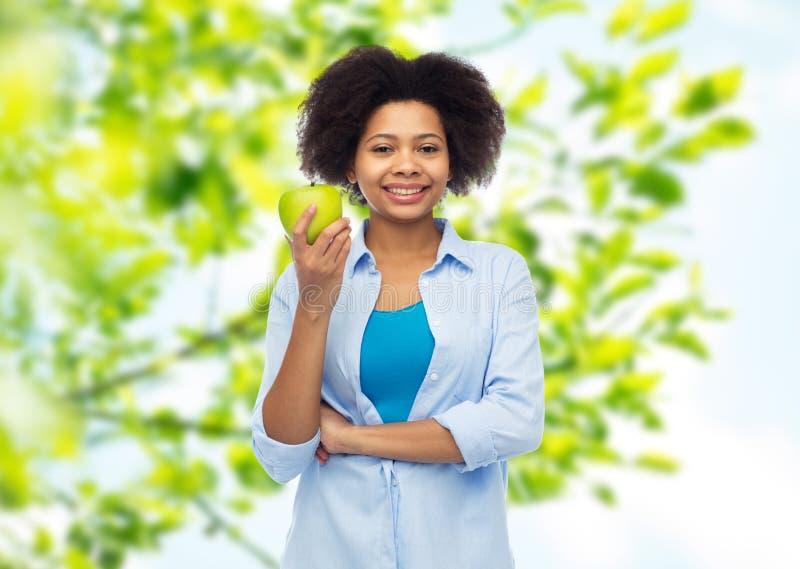 Szczęśliwa amerykanin afrykańskiego pochodzenia kobieta z zielonym jabłkiem fotografia stock