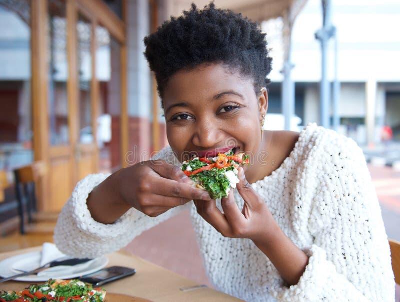 Szczęśliwa amerykanin afrykańskiego pochodzenia kobiety łasowania pizza zdjęcia stock