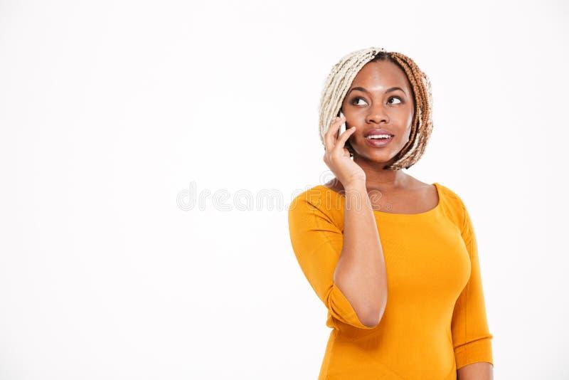 Szczęśliwa amerykanin afrykańskiego pochodzenia kobiety pozycja i opowiadać na telefonie komórkowym obrazy royalty free