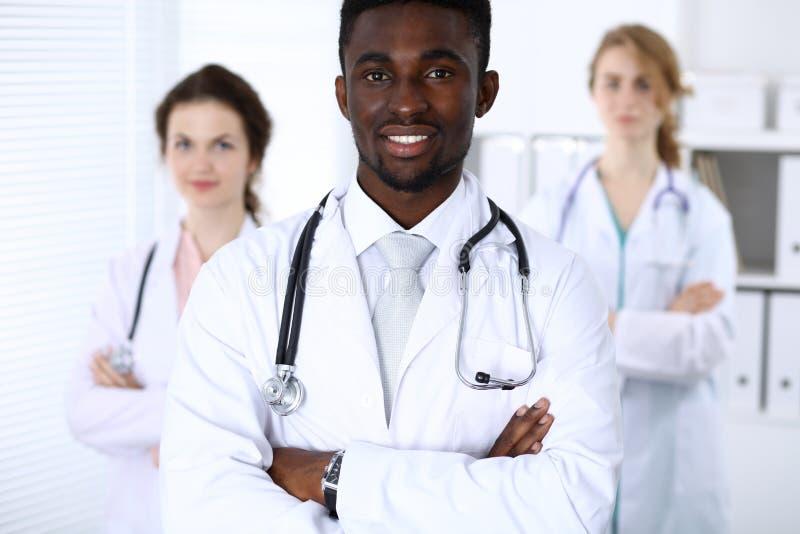 Szczęśliwa amerykanin afrykańskiego pochodzenia lekarka z personelem medycznym przy szpitalem Wielo- etniczni ludzie grup obraz stock
