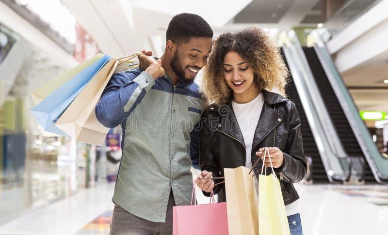 Szczęśliwa amerykanin afrykańskiego pochodzenia para dyskutuje zakupy i ono uśmiecha się zdjęcie stock