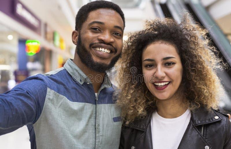 Szczęśliwa amerykanin afrykańskiego pochodzenia para robi selfie i ono uśmiecha się fotografia royalty free