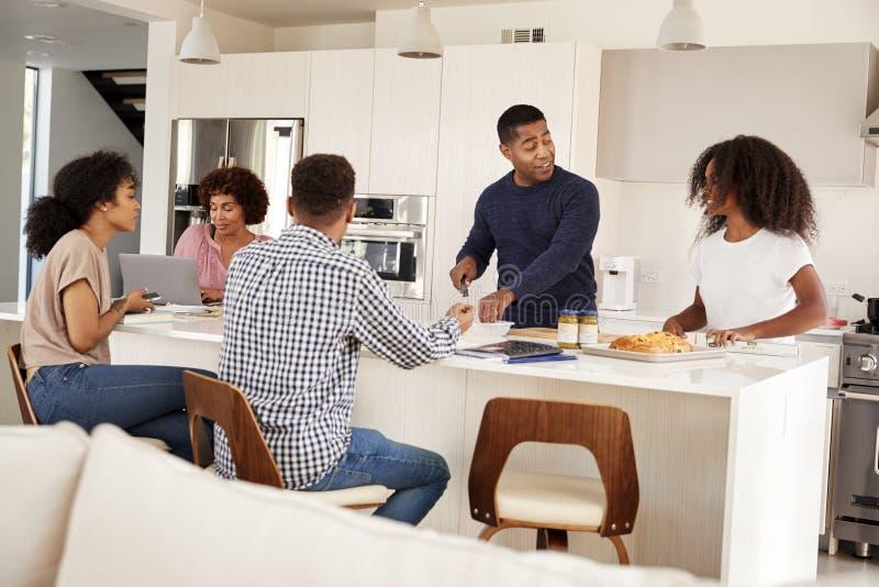 Szczęśliwa amerykanin afrykańskiego pochodzenia rodzina przy ich kuchenną wyspą opowiada rodzinnego posiłek wpólnie i przygotowyw zdjęcia royalty free