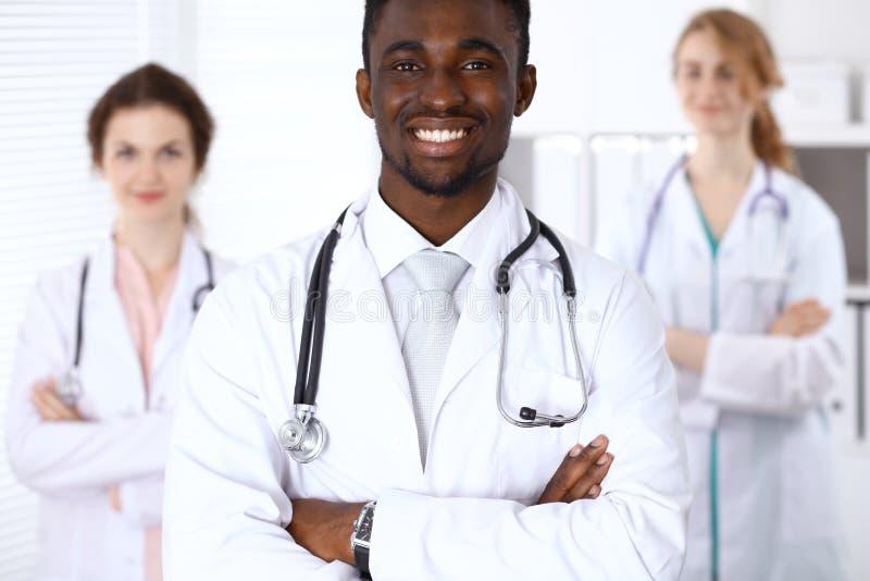 Szczęśliwa amerykanin afrykańskiego pochodzenia samiec lekarka z medycznym personelem przy szpitalem pojęcie kłama medycyny pieni fotografia royalty free