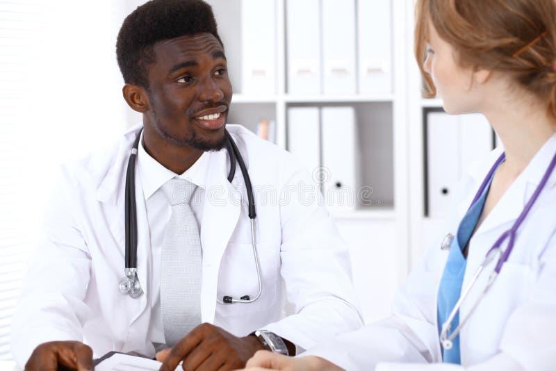 Szczęśliwa amerykanin afrykańskiego pochodzenia samiec lekarka z medycznym personelem przy szpitalem pojęcie kłama medycyny pieni zdjęcia stock
