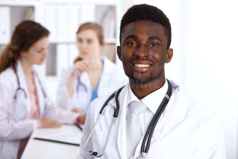 Szczęśliwa amerykanin afrykańskiego pochodzenia samiec lekarka z medycznym personelem przy szpitalem pojęcie kłama medycyny pieni zdjęcia royalty free