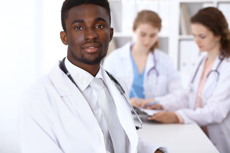 Szczęśliwa amerykanin afrykańskiego pochodzenia samiec lekarka z medycznym personelem przy szpitalem pojęcie kłama medycyny pieni obraz stock