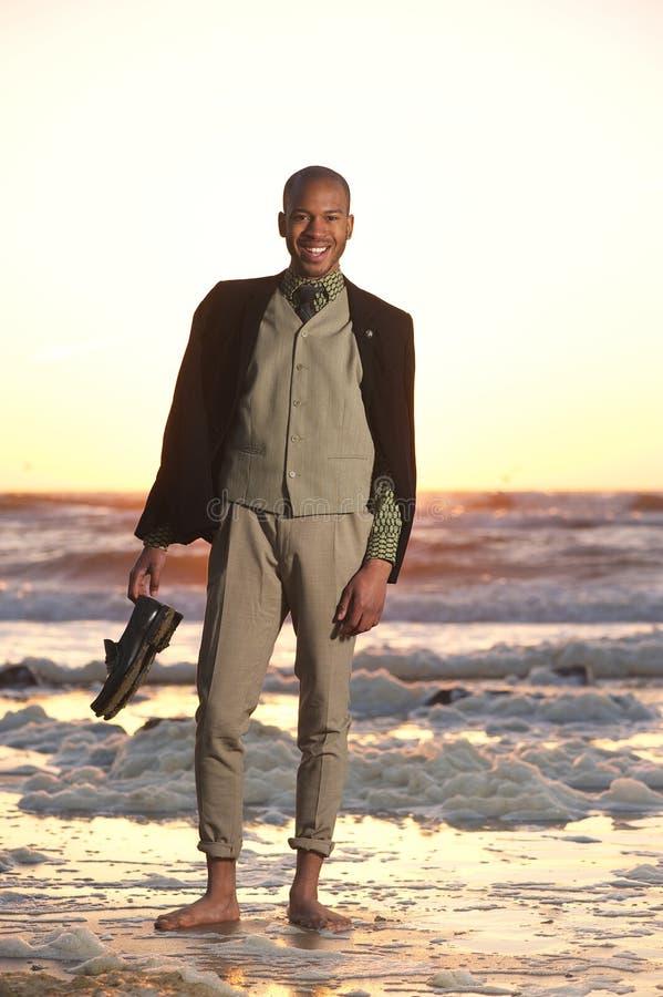 Szczęśliwa amerykanina afrykańskiego pochodzenia mężczyzna pozycja na plaży obrazy stock