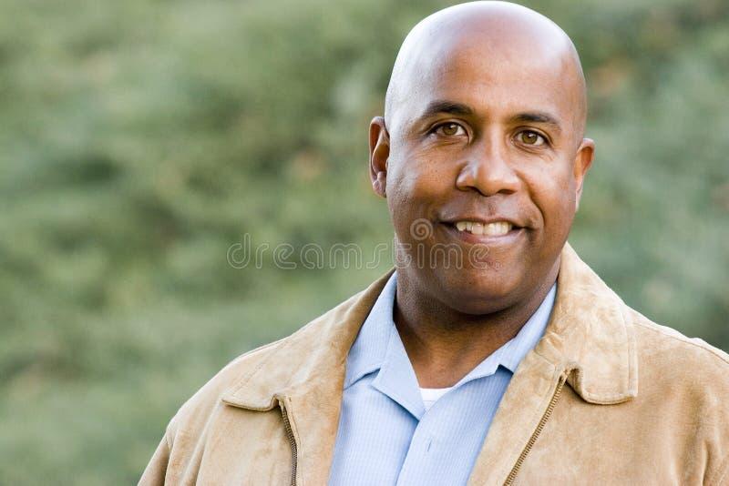 Szczęśliwa amerykanina afrykańskiego pochodzenia mężczyzna pozycja na zewnątrz ono uśmiecha się obrazy royalty free