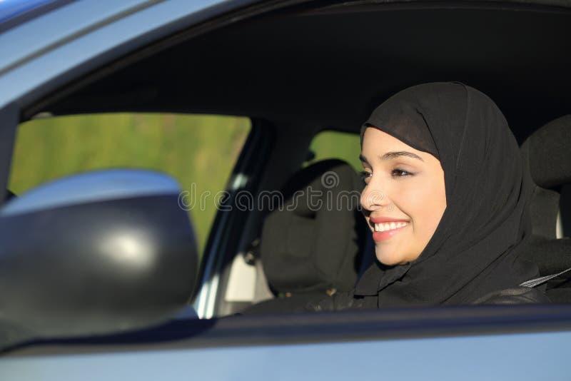 Szczęśliwa arabska saudyjska kobieta jedzie samochód obraz stock