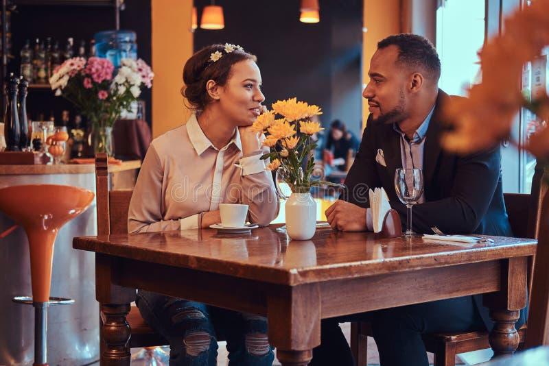 Szczęśliwa atrakcyjna afroamerykańska para w miłości ma wielkiego czas w restauraci przy ich datowanie wpólnie A zdjęcia royalty free