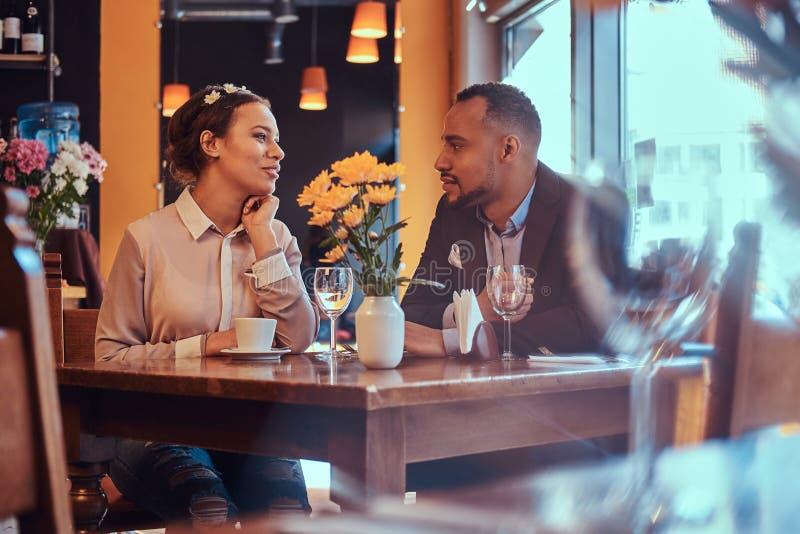 Szczęśliwa atrakcyjna afroamerykańska para w miłości ma wielkiego czas w restauraci przy ich datowanie wpólnie A fotografia royalty free