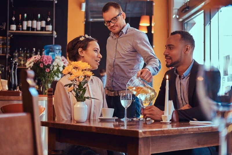 Szczęśliwa atrakcyjna afroamerykańska para w miłości ma wielkiego czas w restauraci przy ich datowanie wpólnie A obrazy stock