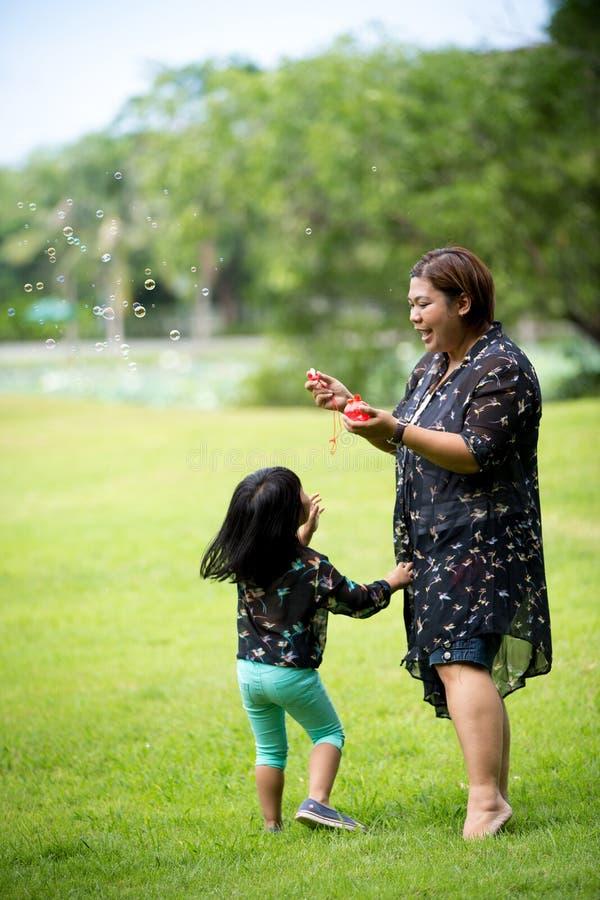 Download Szczęśliwa Azjata Matka, Córka Iblowing Mydlanych Bąble I Obraz Stock - Obraz złożonej z bąbel, dziecko: 57650365