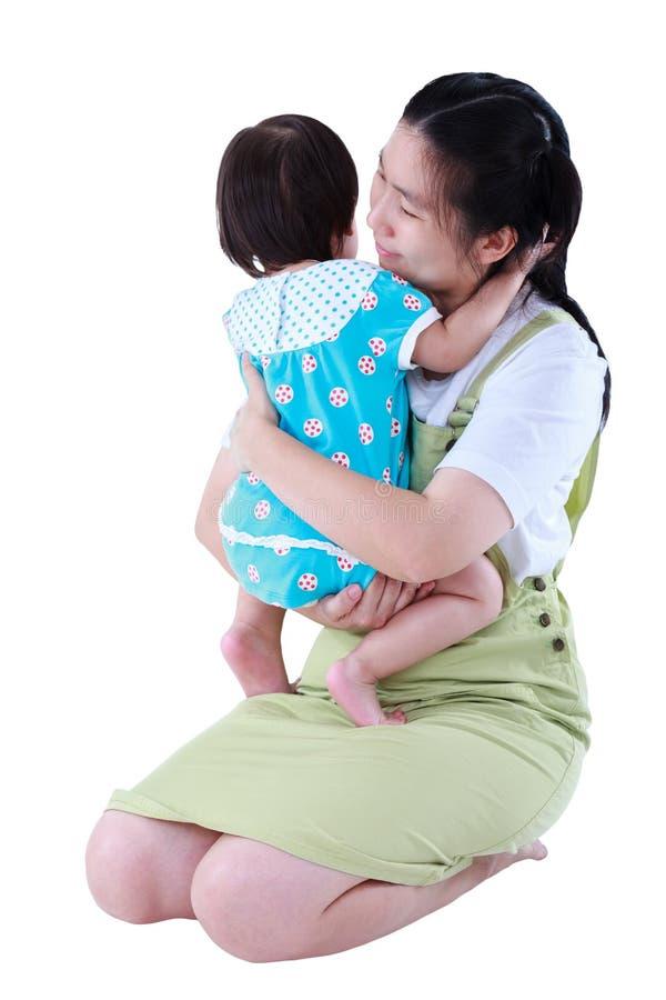 Szczęśliwa azjata matka niesie jej córki Odizolowywający na bielu plecy obraz stock