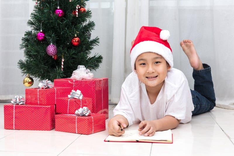 Szczęśliwa Azjatycka Chińska chłopiec writing książka obok bożych narodzeń pre zdjęcia stock
