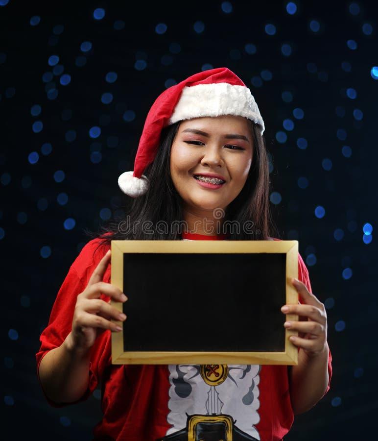 Szczęśliwa Azjatycka dziewczyna Jest ubranym Santa Kostiumowego Bożenarodzeniowego mienia Małego b fotografia royalty free