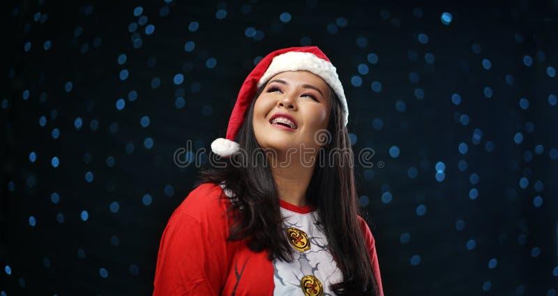 Szczęśliwa Azjatycka dziewczyna Jest ubranym Santa zmroku łuny Kostiumowego Bożenarodzeniowego śnieg obrazy royalty free