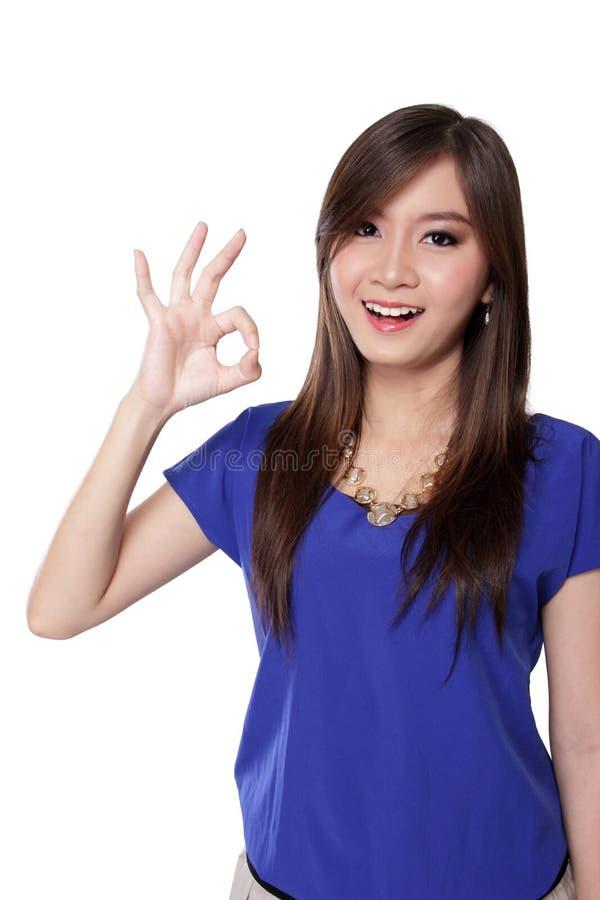 Szczęśliwa Azjatycka dziewczyna robi ok znakowi, odosobnionemu na bielu zdjęcia royalty free
