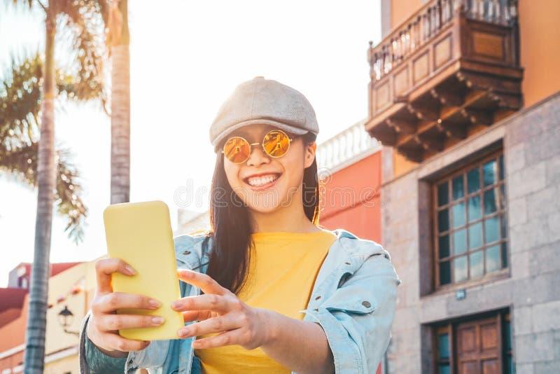 Szczęśliwa Azjatycka dziewczyna używa mobilnego smartphone plenerowego - Chiński ogólnospołeczny influencer ma zabawę robi wideo  zdjęcie royalty free