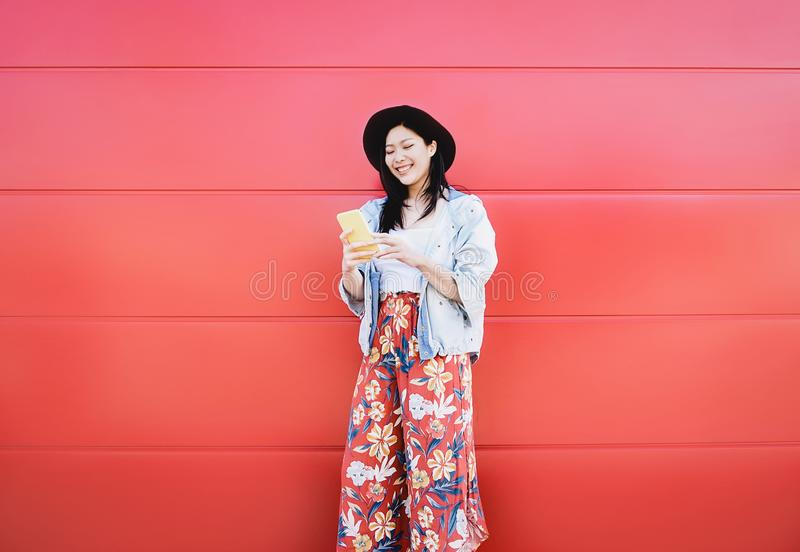 Szczęśliwa Azjatycka dziewczyna używa telefon komórkowego plenerowego - Chiński ogólnospołeczny influencer ma zabawę z nowymi tre zdjęcie stock