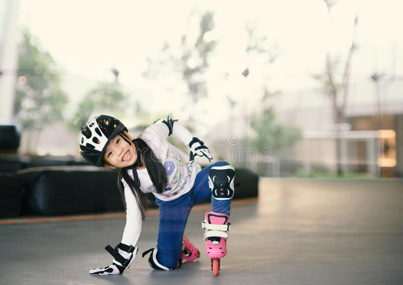 Szczęśliwa Azjatycka dziewczyna uczy się rolkowa łyżwa Dzieci jest ubranym ochrona ochraniacz?w dla bezpiecznej przeja?d?ki Aktyw fotografia royalty free