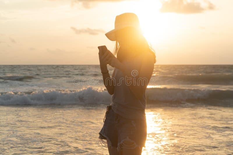 Szczęśliwa Azjatycka kobieta używa telefon komórkowego lub texting wiadomości na ogólnospołecznych środkach przy plażą podczas po obrazy royalty free