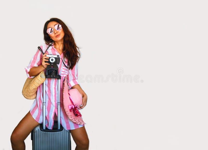 Szczęśliwa Azjatycka kobieta z walizką i biletem stoi blisko ściany obraz royalty free