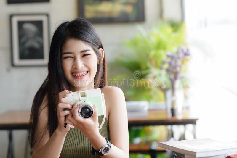 Szczęśliwa Azjatycka kobiety mienia rocznika kamera w kawiarni, styl życia conc obrazy royalty free