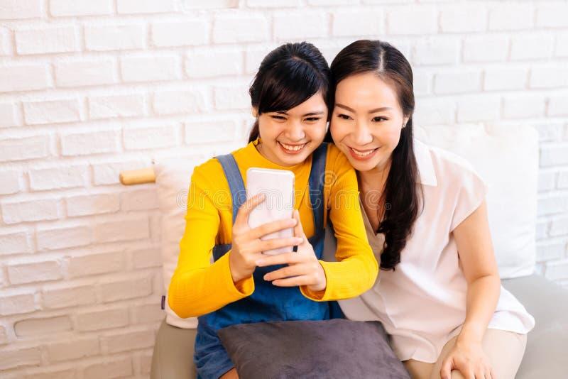 Szczęśliwa Azjatycka nastoletnia córka i w średnim wieku matka bierze selfie lub wideo dzwonić obrazy royalty free