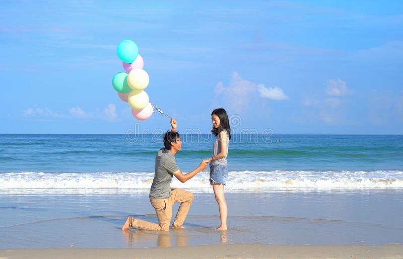 Szczęśliwa Azjatycka para trzyma kolorowych balony przy plażą podczas podróży wycieczki na wakacjach być na wakacjach outdoors pr obraz royalty free