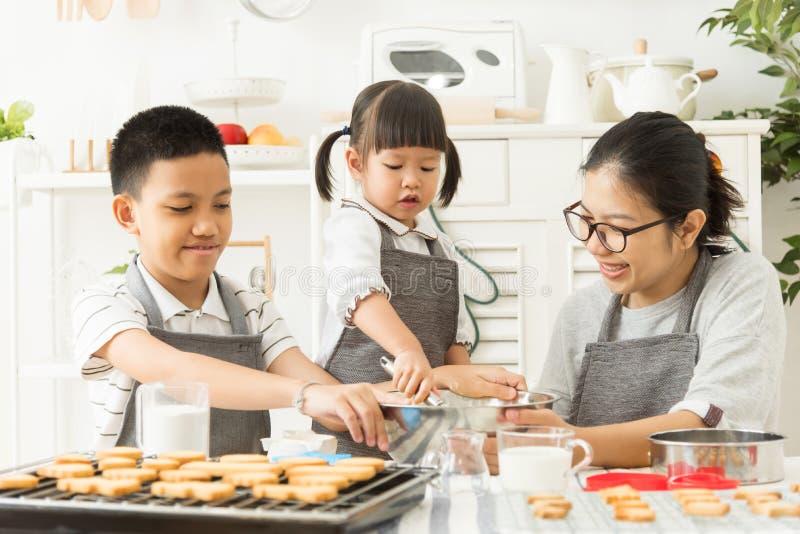 Szczęśliwa Azjatycka rodzina przygotowywa ciasto zdjęcia royalty free