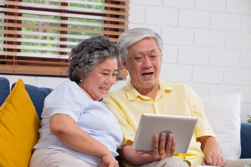 Szczęśliwa Azjatycka starsza para używa pastylki wideo gawędzenie rodzina w domu starze? si? w domu poj?cie zdjęcia stock