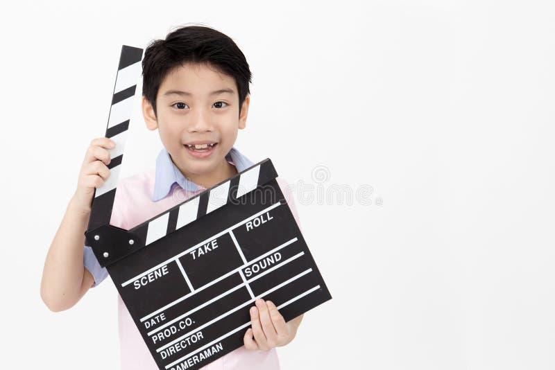Szczęśliwa azjatykcia chłopiec mienia clapper deska w rękach Kinowy pojęcie zdjęcia stock