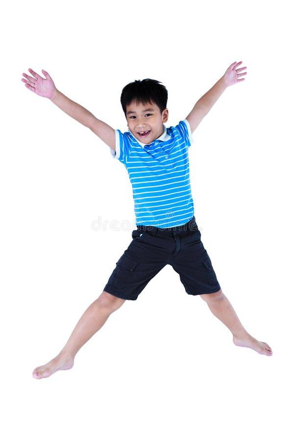 Szczęśliwa azjatykcia chłopiec ono uśmiecha się i skacze, odizolowywający na białym backgroun zdjęcia royalty free
