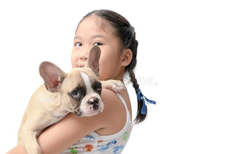 Szczęśliwa azjatykcia dzieciak dziewczyna trzyma francuskiego buldoga obraz stock