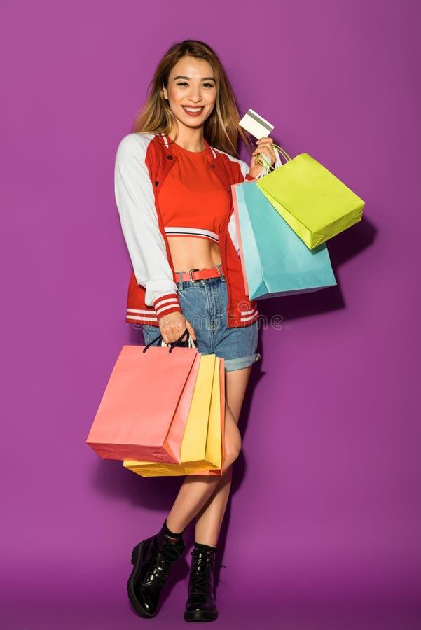 szczęśliwa azjatykcia dziewczyna trzyma kartę kredytową i ono uśmiecha się przy kamerą z torbami na zakupy zdjęcia stock