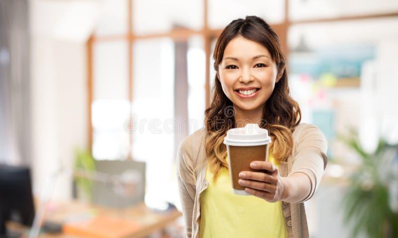 Szczęśliwa azjatykcia kobieta pije kawę przy biurem zdjęcie stock