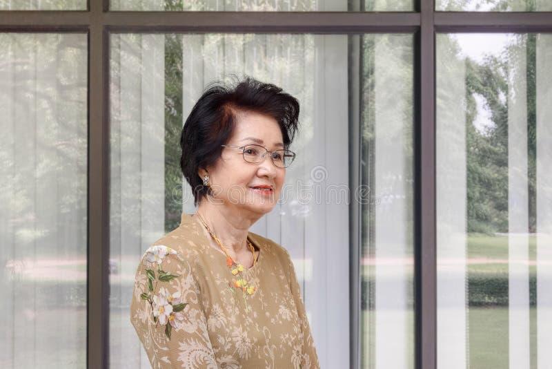 Szczęśliwa azjatykcia kobieta relaksuje w domu w żywym pokoju obraz stock